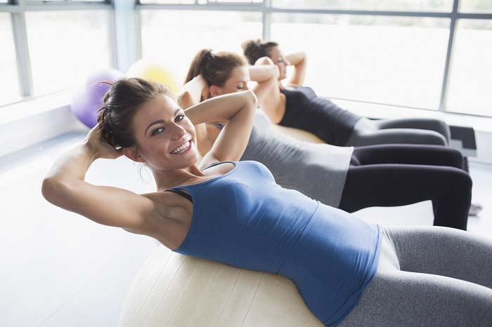 Three women doing sit-ups on exercise balls in gym