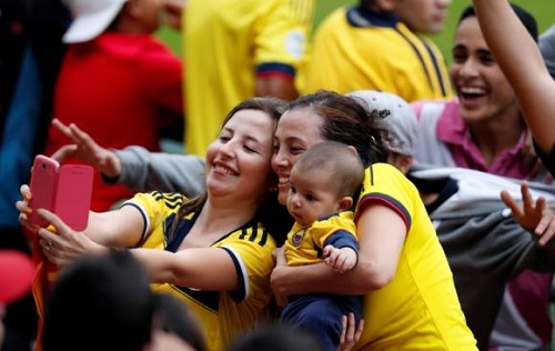 Soccer fans take a photograph during Colombia's national soccer team training session in Cotia